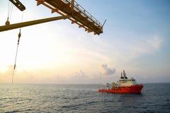 Zaopatrzeniowa łódkowata operacja wysyła jakaś kosz lub ładunek na morzu Wspiera przeniesienie na morzu ropa i gaz przemysł jakaś Zdjęcie Stock