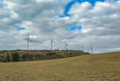 Zaorany pole i wzgórze z wiatraczkami w spadku fotografia stock