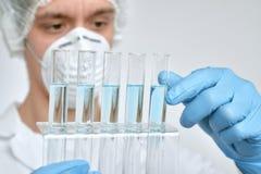 Zapalony naukowiec w ochronnej odzieży wykonuje proteinowego assay zdjęcia stock