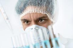 Zapalony naukowiec z brązów oczami w ochronnej odzieży ładuje próbki zdjęcie royalty free