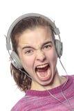 Zapalony rozkrzyczany żeński nastolatek z hełmofonami obraz stock