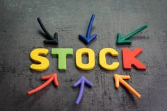Zapas lub rynek akcji, inwestorski wartości pojęcie, strzały wskazuje centrum z kolorowymi listami buduje słowo zapas obrazy royalty free