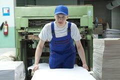 Zapas odsadzki papier Mężczyzna pracuje w druk fabryce obrazy royalty free