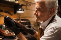 Zapatero concentrado en el taller que hace los zapatos fotos de archivo libres de regalías