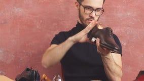 Zapatero impresionante joven con los vidrios que buscan defectos en las manos del hombre almacen de video