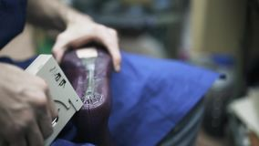 Zapatero que sujeta con grapa la bota púrpura de la mujer s metrajes