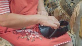 Zapateros de las manos de la mujer mayor del primer que anudan cordones de zapato en una manta del zapato que se sienta en una bu almacen de video