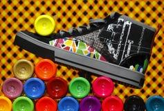 Zapatilla de deporte del color que se coloca en las botellas de la pintura Fotografía de archivo libre de regalías