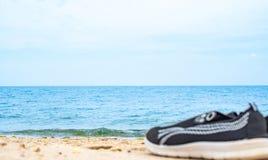 Zapatilla de deporte negra corriente en lado de la playa del agua azul imagen de archivo libre de regalías
