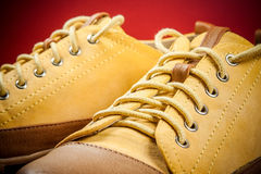 Zapatillas de deporte amarillas en fondo rojo Imagenes de archivo