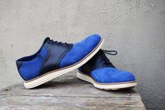 Zapatillas de deporte azul marino con un lenguado blanco en un fondo de madera foto de archivo libre de regalías
