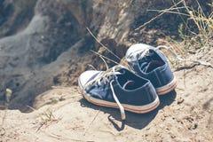 Zapatillas de deporte azules de la juventud en la tierra Foto de archivo libre de regalías