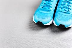 Zapatillas de deporte azules en la estera gris para entrenar Fotos de archivo libres de regalías