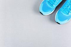 Zapatillas de deporte azules en la estera gris para entrenar Foto de archivo