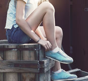 Zapatillas de deporte azules en las piernas de la muchacha en el fondo del grunge Foto de archivo