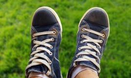 Zapatillas de deporte azules en las piernas de un muchacho Fotografía de archivo libre de regalías