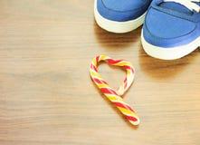 Zapatillas de deporte azules Fondo de madera Caramelo en la forma de un corazón quebrado Se espera que usted abandone de lo que u Imagenes de archivo