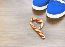 Zapatillas de deporte azules Fondo de madera Caramelo en la forma de un corazón quebrado Se espera que usted abandone de lo que u Foto de archivo libre de regalías