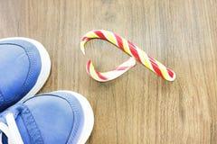 Zapatillas de deporte azules Fondo de madera Caramelo en la forma de un corazón quebrado Se espera que usted abandone de lo que u Fotografía de archivo libre de regalías