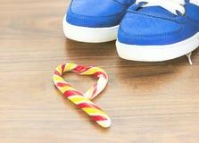 Zapatillas de deporte azules Fondo de madera Caramelo en la forma de un corazón quebrado Se espera que usted abandone de lo que u Imagen de archivo