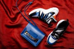 Zapatillas de deporte blancas con los partes movibles negros y azules en un lenguado figurado grueso y un bolso azul con una cade imagenes de archivo