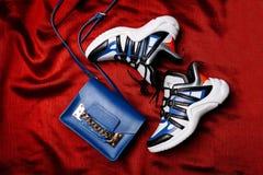 Zapatillas de deporte blancas con los partes movibles negros y azules en un lenguado figurado grueso y un bolso azul con una cade imagen de archivo