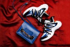 Zapatillas de deporte blancas con los partes movibles negros y azules en un lenguado figurado grueso y un bolso azul con una cade fotografía de archivo libre de regalías
