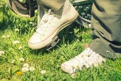 Zapatillas de deporte blancas en las piernas del ` s de la mujer en una bici Fotos de archivo