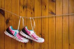 Zapatillas de deporte blancas y rosadas que cuelgan en la cuerda para tender la ropa (en una cuerda) o imágenes de archivo libres de regalías