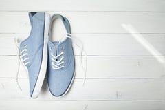 Zapatillas de deporte casuales del verano en un fondo de madera blanco Copie el espacio para el texto foto de archivo libre de regalías