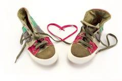 Zapatillas de deporte con el símbolo rosado del corazón hecho de cordones Fotos de archivo libres de regalías