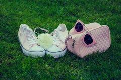 Zapatillas de deporte con la rosa, el monedero y las gafas de sol del blanco Imagen de archivo libre de regalías