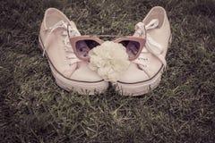 Zapatillas de deporte con la rosa y las gafas de sol del blanco con la hierba como backgrou Foto de archivo libre de regalías