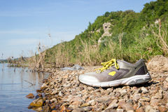 Zapatillas de deporte con los cordones amarillos cerca del agua, playa con las piedras Imagenes de archivo