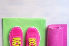 Zapatillas de deporte con una manta y las toallas para los deportes en el piso ligero Imagen de archivo