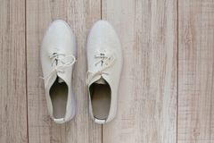 Zapatillas de deporte de cuero blancas en fondo de madera fotos de archivo libres de regalías