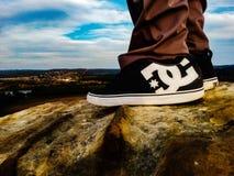 Zapatillas de deporte de DC en la roca Foto de archivo libre de regalías