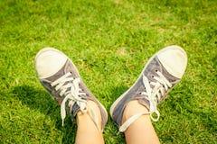 Zapatillas de deporte de la juventud en las piernas de la muchacha en hierba Imagen de archivo