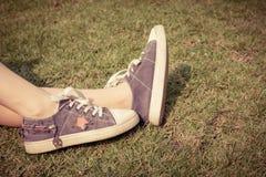 Zapatillas de deporte de la juventud en las piernas de la muchacha en hierba Fotografía de archivo