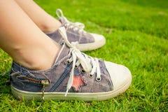 Zapatillas de deporte de la juventud en las piernas de la muchacha en hierba Imagenes de archivo