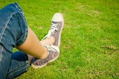 Zapatillas de deporte de la juventud en las piernas de la muchacha en hierba Fotos de archivo