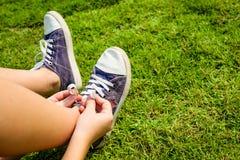 Zapatillas de deporte de la juventud en las piernas de la muchacha en hierba Imágenes de archivo libres de regalías