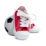 Zapatillas de deporte de los niños y balón de fútbol Imagen de archivo libre de regalías