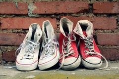 Zapatillas de deporte de los pares que se inclinan contra una pared de ladrillo Fotos de archivo