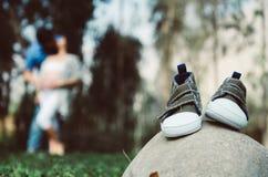 Zapatillas de deporte del bebé en una piedra, con el fondo borroso de los padres fotografía de archivo