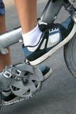 Zapatillas de deporte del muchacho y pedales de la bicicleta Fotos de archivo
