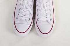 Zapatillas de deporte elegantes de la juventud en un fondo blanco Foto de archivo libre de regalías