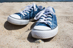 Zapatillas de deporte en la arena blanca Fotografía de archivo