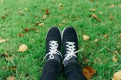 Zapatillas de deporte en las piernas de la muchacha en hierba durante día de verano sereno soleado Foto de archivo