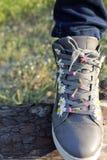Zapatillas de deporte en margaritas Imagenes de archivo